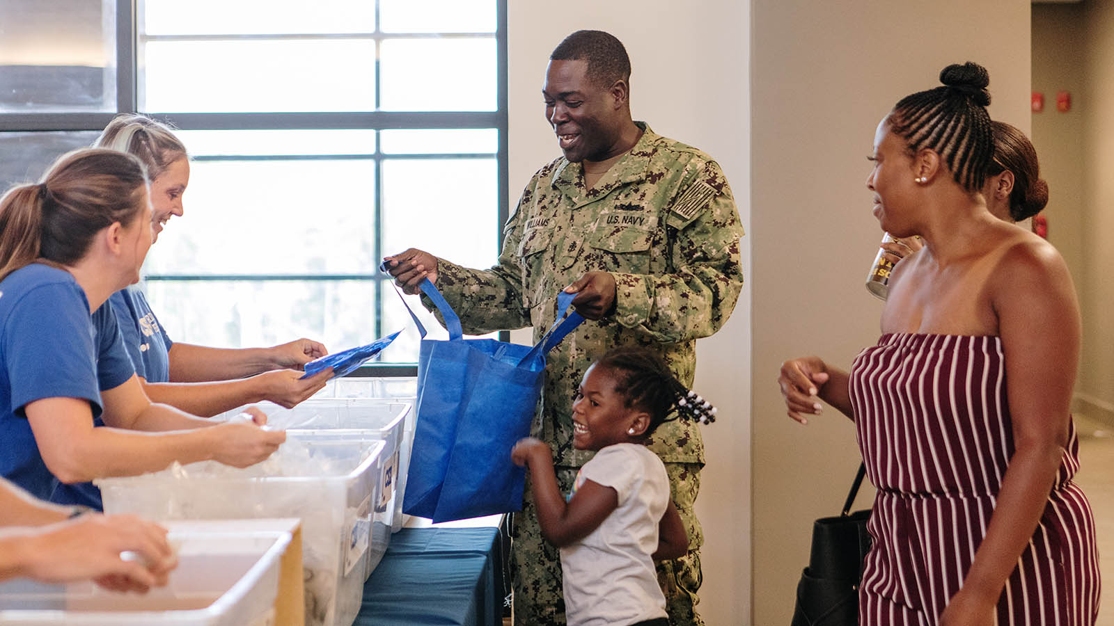 Service Member helps daughter pick out school supplies at a Back-to-School Brigade