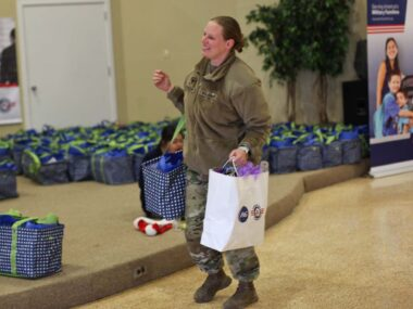 Service member carrying two bags full of food at a Holiday Meals for Military event.