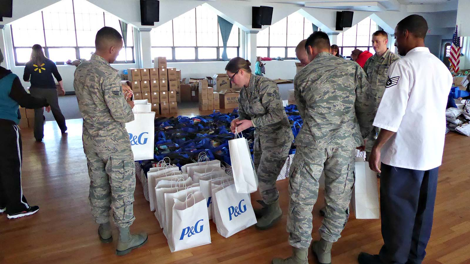 Several service members picking up P&G bags of food during a Holiday Meals for Military event.