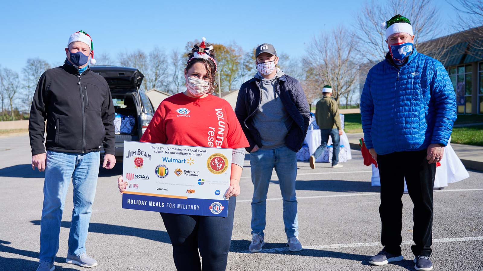 Four Operation Homefront volunteers standing outside in a parking lot holding a sign for the Holiday Meals for Military event.