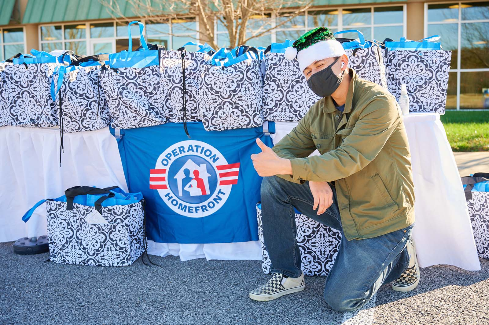 Operation Homefront volunteer kneeling down by a bunch of bags full of food for the Holiday Meals for Military program.