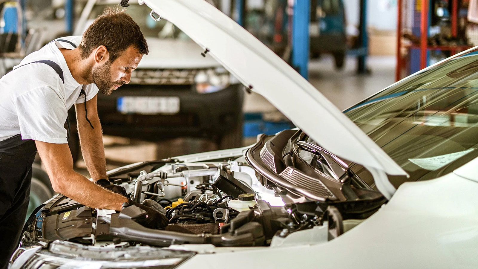 Man working under the hood of a white vehicle.