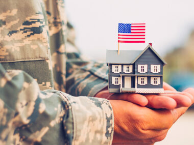 Service member holding a miniature house in his hands.