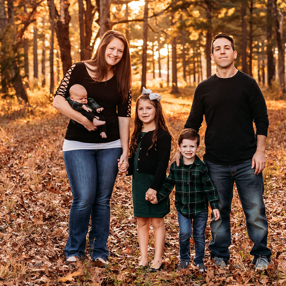 A man and woman and three kids in a family photo