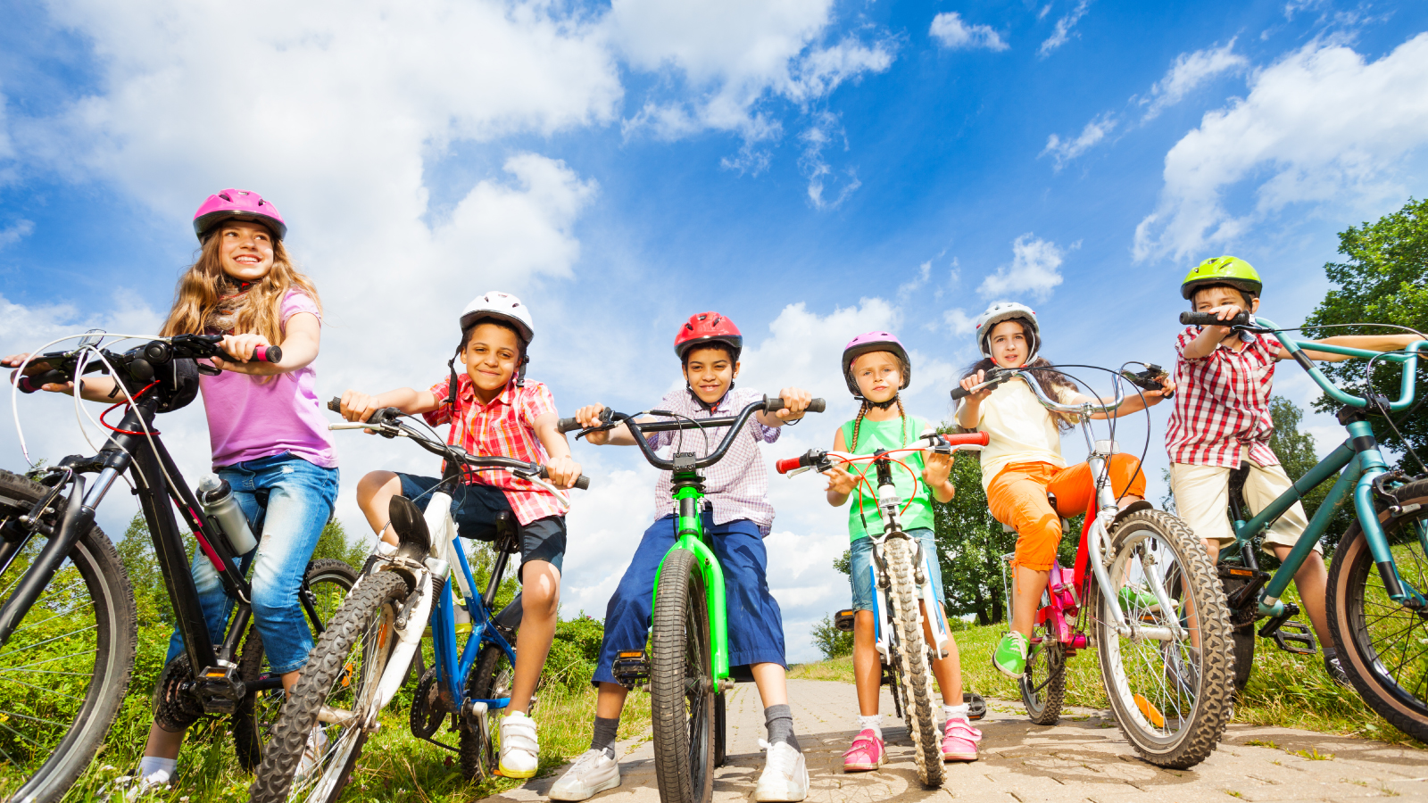 4 kids sitting on their bikes in the sun with the clouds rolling by overhead.