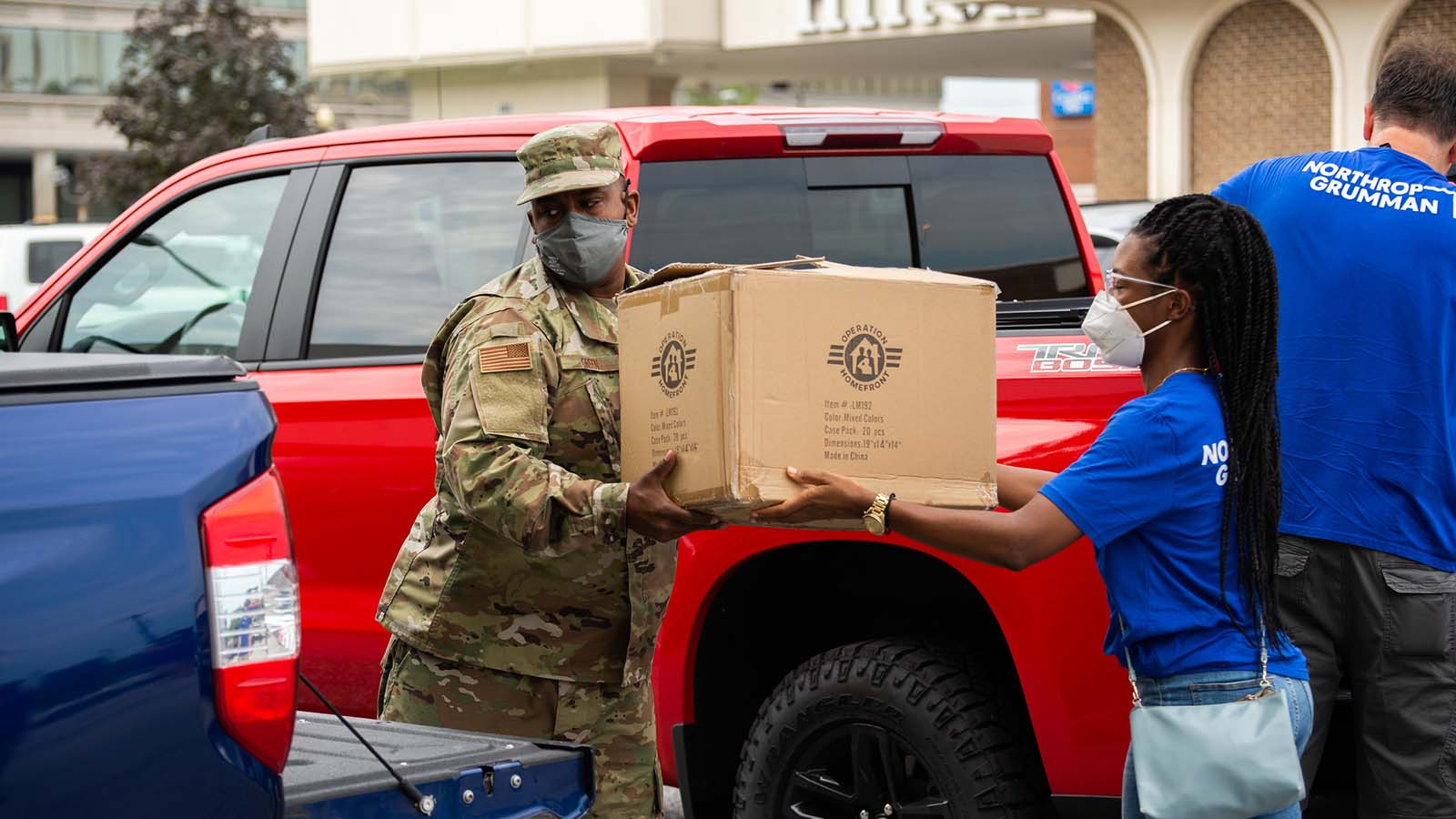 Service member is receiving a large box from a Northrop Grumman volunteer at an Operation Homefront Back-to-School Brigade event.