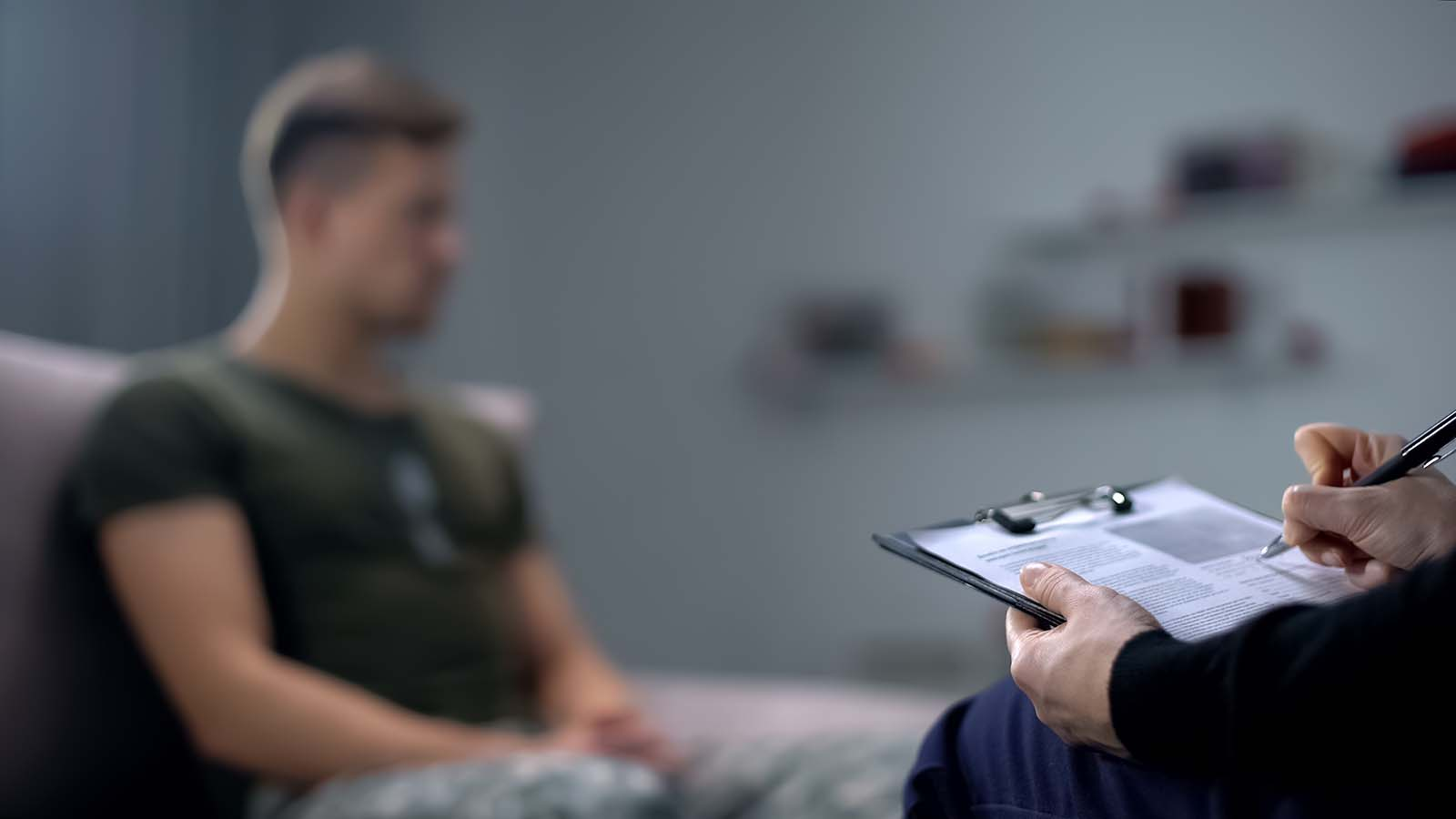 Service member sits on couch while a counselor takes notes. The counselor is sitting across from the service member.